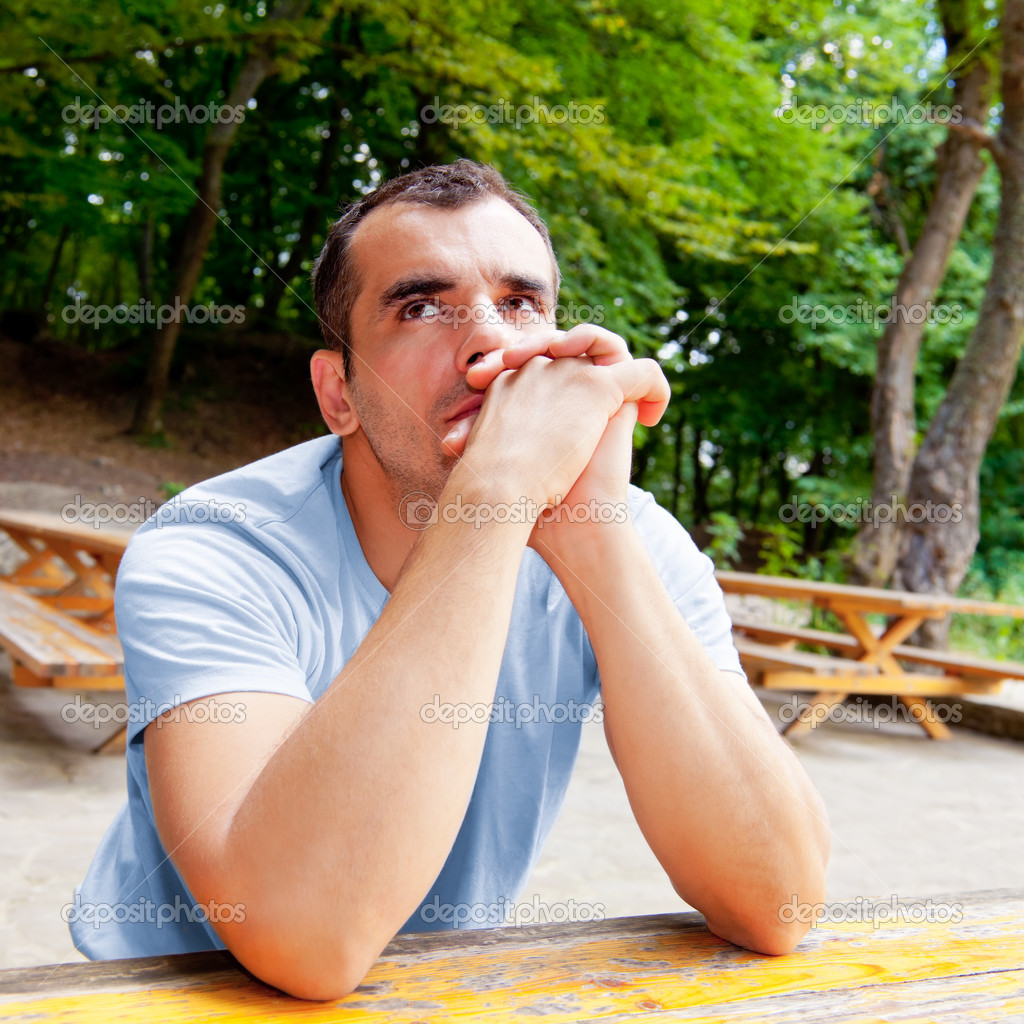 Portrait of thoughtful man with arms on the table; outdoors — Stock Photo #8089126