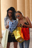 Two girls with vibrant shoping bags — Stock Photo