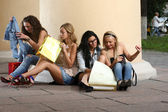 Four girls with vibrant shoping bags — Stock Photo