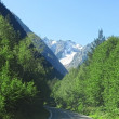 Road leads to caucasus mountains. Summer and snow — Stock Photo