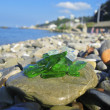 Green and white broken glass on the summer beach — Stock Photo