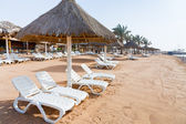 Plastic beach beds on coral bay in Aqaba — Stock Photo
