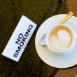 Cup of cappuccino  on no-smoking table — Stock Photo