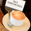 Cup of cappuccino  on no-smoking table — Lizenzfreies Foto