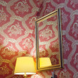 Foto Stock: Yellow retro lamp and red vintage silk wallpaper