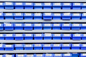 Blue plastic boxes in storage stand — Stock Photo