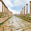 Long colonnaded street in antique town Jerash - Stock Photo