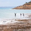Stock Photo: In mineral mud in Dead Sea, Jordan