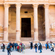 Tourists near gate of Treasury Monument in antique city Petra - Stock Photo