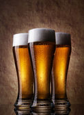 Three cold Beer into glass on a old stone — Stock Photo
