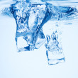 A background of bubbles forming in blue water after ice cubes ar — Stock Photo