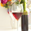 Wine glasses filled with red wine and wine bottle — Stock Photo