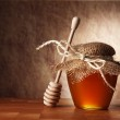 Pot of honey and wooden stick are on a table. — Stock Photo