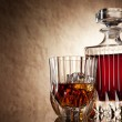 Постер, плакат: Glass and decanter of brandy on a old stone background