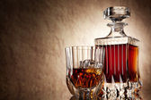 Glass and decanter of brandy on a old stone background — Stock Photo