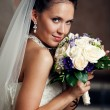 Young happy bride with flowers — Stock Photo