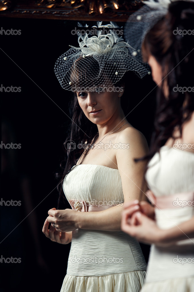 Happy bride watchs in the mirror indoors — Stock Photo #9592074