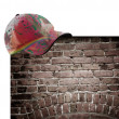Music and rainbow colored hat on the brick wall — Stock Photo #8254530