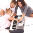 Family playing piano — Stock Photo