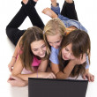 Three young girls and laptop — Stock Photo
