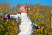 Old man with dumb bells — Stock Photo