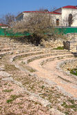 Steps of ancient theater and modern buildings — Stock Photo