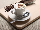 Cup of coffee with a skin and coffee grains — Stock Photo