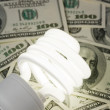 Compact Fluorescent Light bulb and dollar — Stock Photo