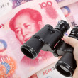 Binoculars and chinese yuan — Stock Photo