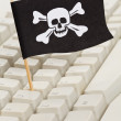 Pirate Flag and Computer Keyboard - Stock Photo