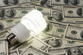 Compact Fluorescent Lightbulb and dollar — Stock Photo