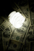 Compact Fluorescent Ligh tbulb and dollar — Stock Photo