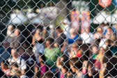 Metal netting and crowd — Stock Photo
