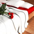 Stock Photo: Beautiful red roses on the bed