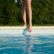 Feet on swimming pool border — 图库照片