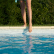 Stock Photo: Feet on swimming pool border