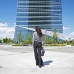 Empresaria caminando a rascacielos — Foto de Stock