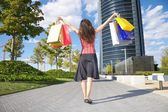 Happy shopper and skyscrapers — Stock Photo