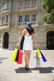 Woman with hat and shopping bags — Stock Photo