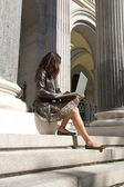 Leather businesswoman sitting with portable — Stock Photo
