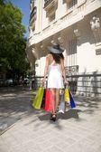 Shopping woman back walking on sidewalk — Stock Photo