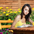 Pretty girl with book in the garden — Stock Photo