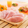 Fresh raw chicken breast arrangement on kitchen cutting board - Stock Photo