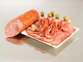 Arrangement with fresh Dry Crakow Sausage on steel silver boar — Stock Photo