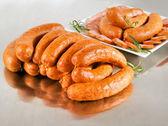 Arrangement with fresh pork sausage on steel silver board. — Stock Photo