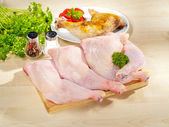 Fresh raw and roasted chicken legs arrangement on kitchen cuttin — Stock Photo