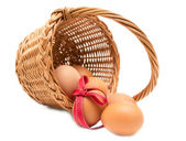 Easter egg wioth red ribbon in a basket isolated on a white back — Stock Photo