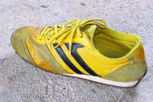 Old yellow shoes on concrete — Stock Photo
