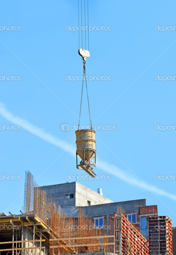 Crane lifting concrete mixer container against blue sky  Stock Photo #10265678
