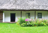 Flowerbed and ancient hut — Stock Photo